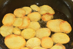 Potatoes on the iron frying pan Stock Images