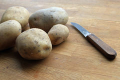 Potatoes with knife on wooden table. Fresh potatoes on wooden table with knife. Peeling potatoes stock photography