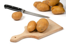 Potatoes on a wooden chopping board. Potatoes and knife  on white background Stock Photography