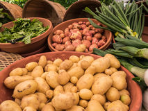 Potatoes and leeks at Corvallis Farmers Market, Oregon. Yukon Gold and red potatoes displayed in pottery bowls with leeks and spinach at Corvallis Farmers Market Stock Photography