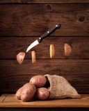 Potatoes with levitate slices and knife Stock Photos