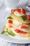 Potatoes with mozzarella, tomato and basil closeup vertical Stock Photo