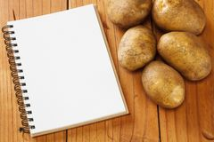 Recipe Book and Potatoes. Potatoes and notebook for your recipe, on an old pine table Stock Photography