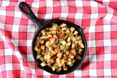 Potatoes Obrien in Skillet on Red Checked Table Cloth. High angle shot of a cast iron skillet with potatoes O'brien on a red checked table cloth Royalty Free Stock Photo