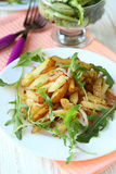 Potatoes with onion and arugula Royalty Free Stock Photos