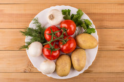 Potatoes, onion, ripe tomatoes, parsley and dill in dish Royalty Free Stock Photos