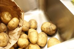 Potatoes and a paper bag in a kicthen sink stock photo