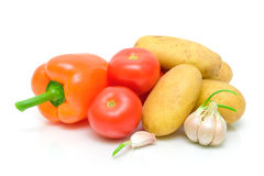 Potatoes, peppers, tomatoes and garlic on a white background Stock Photography
