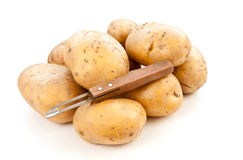 Potatoes with potato peeler Royalty Free Stock Photography