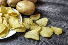 Potatoes and potato products, fried potato slices, potato slices fried serrated, fried potato flakes in a furnace,  Potato and pot Stock Image