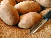Potatoes and potatoe peeler. Potatoes in a burlap potatoe bag with a potatoe peeler royalty free stock photography