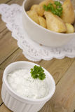Potatoes with quark. Potatoes with herbed quark on a wooden table Royalty Free Stock Photo