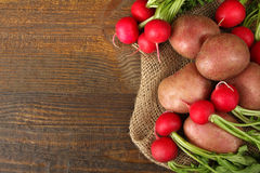 Potatoes  with radishes. Red potatoes with radishes on sackcloth on wooden brown background Stock Photos