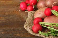 Potatoes  with radishes. Red potatoes with radishes on sackcloth on wooden brown background Stock Image