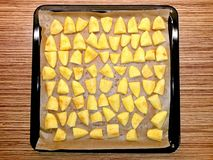 Potatoes raw on baking paper in baking tray. Image royalty free stock photography