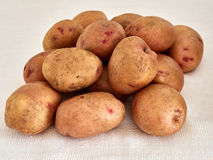 Potatoes. Raw potatoes on a white tablecloth Royalty Free Stock Photo