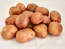 Potatoes. Raw potatoes on a white tablecloth Stock Image
