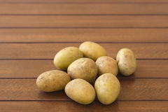 Potatoes. Raw potatoes on wooden background Royalty Free Stock Photography