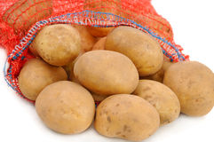 Potatoes in red bag Stock Images