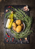 Potatoes with rosemary, spices and bottle of oil on dark slate Royalty Free Stock Photo