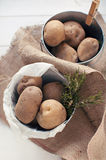 Potatoes and rosemary in tin buckets. On hessian Royalty Free Stock Photography
