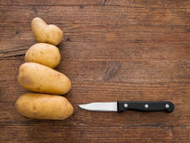 Potatoes on rustic board with knife. Stock Image