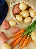 Potatoes in a sack and carrots on a wooden table Stock Photo