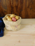 Potatoes in a sack on a wooden background Stock Images