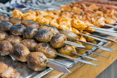 Potatoes and shish kebab on skewers fried on grill outdoors Royalty Free Stock Images