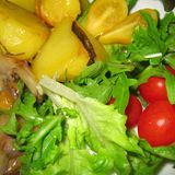 Potatoes and side salad. With cherry tomatoes Stock Image