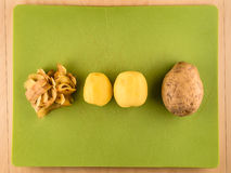 Potatoes, skins in center of green plastic board. Two unpeeled and one peeled potatoes with skinsin center of green plastic board, simple food preparation Stock Photo