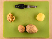 Potatoes and skins on green plastic board. Several unpeeled and peeled potatoes with skins on green plastic board with peeler, simple food preparation Royalty Free Stock Photo