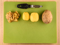 Potatoes, skins and peeler with copyspace. Two unpeeled and one peeled potatoes with skins on green plastic board with peeler, simple food preparation Stock Photo