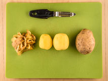 Potatoes, skins and peeler on green plastic board. Two unpeeled and one peeled potatoes with skins on green plastic board with peeler, simple food preparation Stock Image