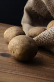 Potatoes Spilling from Sack on to Wood Plank Table Royalty Free Stock Photos