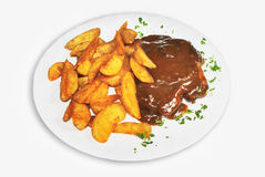 Potatoes and steak with brown sauce. Potatoes and veal steak with demi-glace sauce on isolated background Royalty Free Stock Photography