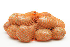 Potatoes in string-bag. On white background royalty free stock photos