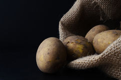 Potatoes Tipping from Hessian Sack on Black Stock Photography