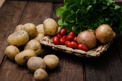 Potatoes with tomatoes on wooden floor.  Royalty Free Stock Image