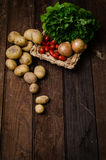 Potatoes with tomatoes on wooden floor.  Royalty Free Stock Photography
