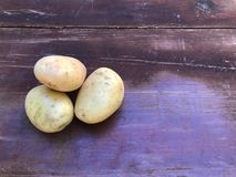 Potatoes unpeeled white-pink against a brown-red old shabby table, isolated royalty free stock photography