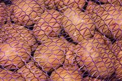 Potatoes vegetables in a grid, mesh bags of potatoes in a truck,. Fresh raw potatoes Royalty Free Stock Image