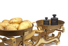 Potatoes on weight. Yellow potatoes on ancient weight Royalty Free Stock Images