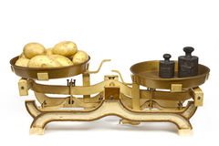 Potatoes on weight. Yellow potatoes on ancient weight. Horizontal position royalty free stock image