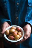 Potatoes in a white bowl in the hands of a man in a blue shirt. Vertical Stock Photos