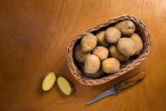 Potatoes in wicker basket on wooden table.Useful as a food backg Stock Photography