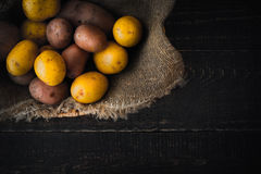 Potatoes in the wicker bowl with canvas on the wooden table Stock Photos