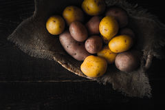Potatoes in the wicker bowl with canvas on the wooden table top view Royalty Free Stock Photo