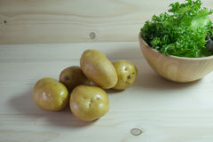 Potatoes on wood table. With green lettuce as background Royalty Free Stock Image