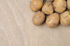 Potatoes on a wooden background and space for text Royalty Free Stock Photos